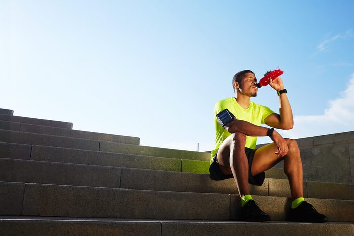 Handsome male runner seated on the steps drink water, beautiful fit man in bright fluorescent sportswear, sports fitness concept
