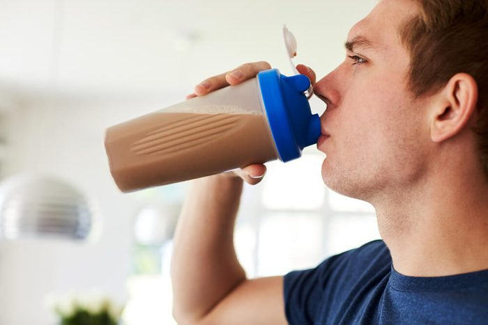 Man Drinking Protein Shake In Kitchen At Home