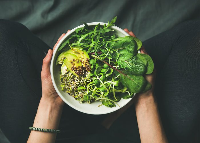 Green vegan breakfast meal in bowl with spinach, arugula, avocado, seeds and sprouts. Girl in leggins holding plate with hands visible, top view. Clean eating, dieting, vegan food concept