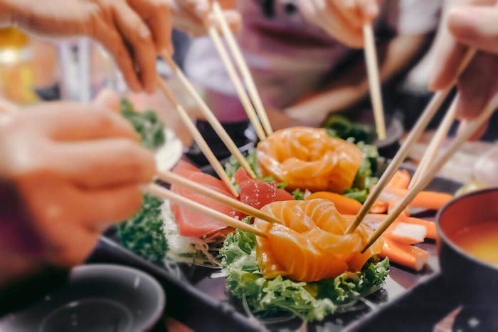 people eating sashimi set in Asian restaurant