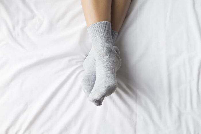 Female feet in warm woolen socks around her feet .Part of the body.Beautiful female legs sitting on the bed. Relax concept.