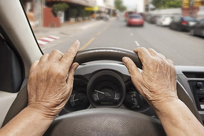 Senior woman driving a car on street in city.