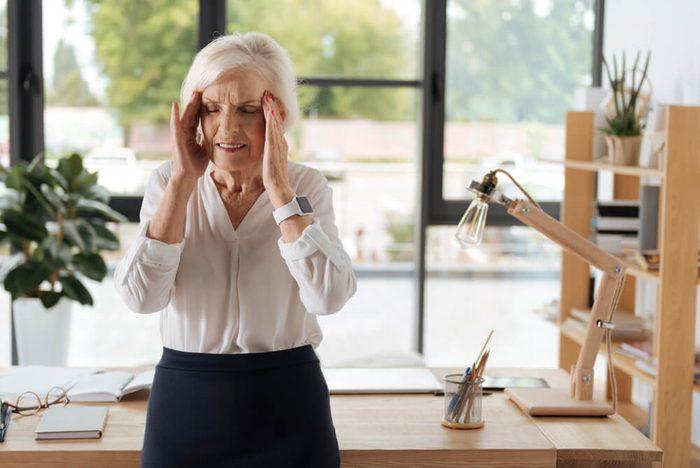 Sad elderly woman suffering from migraine