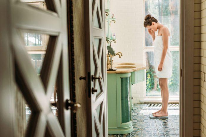 woman weighing herself in bathroom