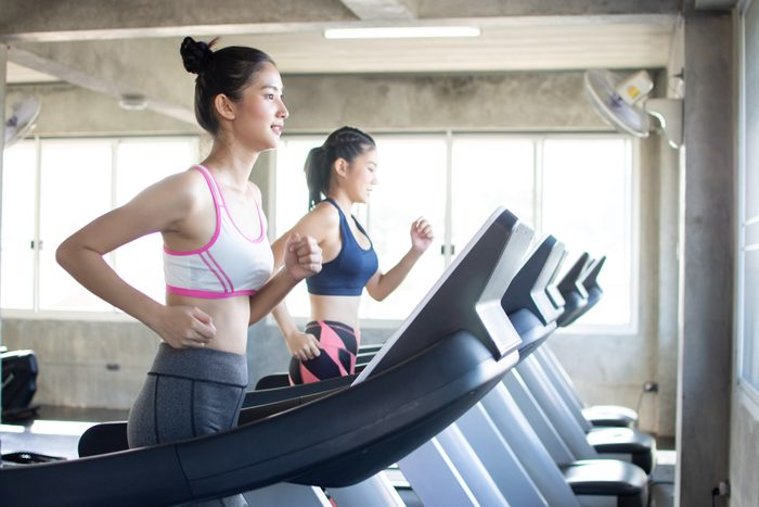 two young women running on treadmils