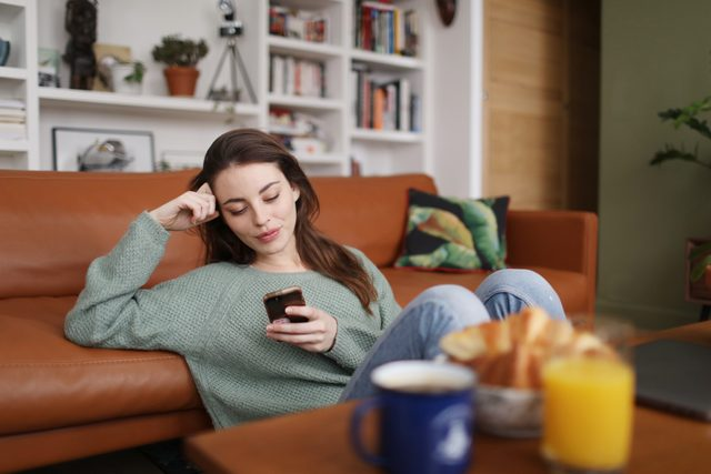 young woman sitting at home alone
