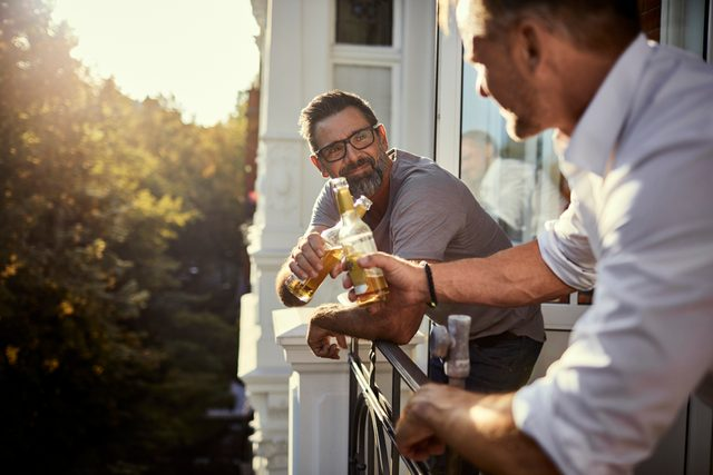 two mature men drinking beer on balcony