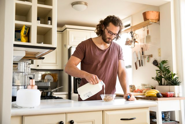man pouring milk into bowl