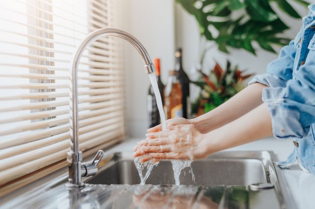 woman washing hands in kitchen sink