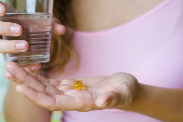 woman holding vitamin and glass of water