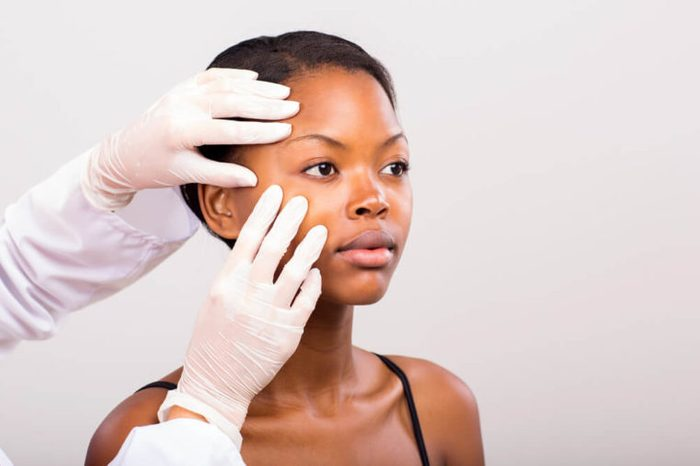 dermatologist checking the skin on a young woman's face