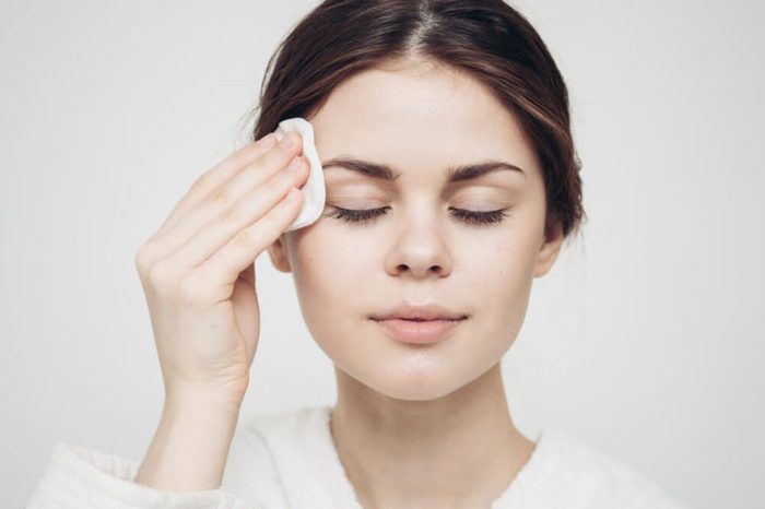 Woman swiping cleansing pad over her face