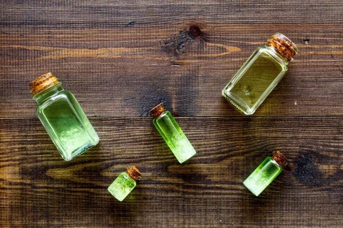 Glass bottles of tea tree oil on a table