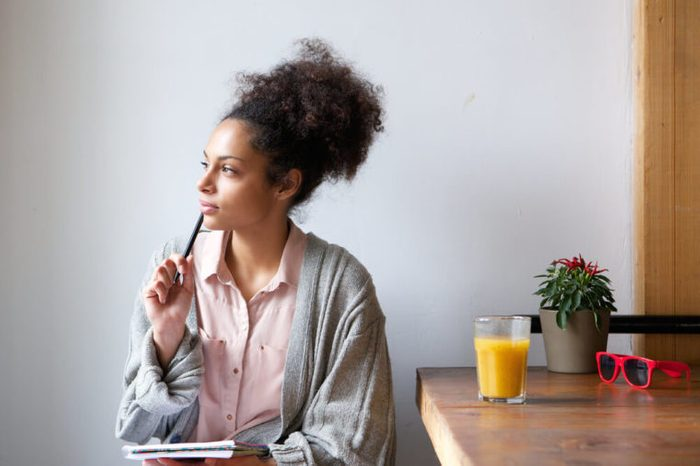 Woman with notepad and pen sitting at a table