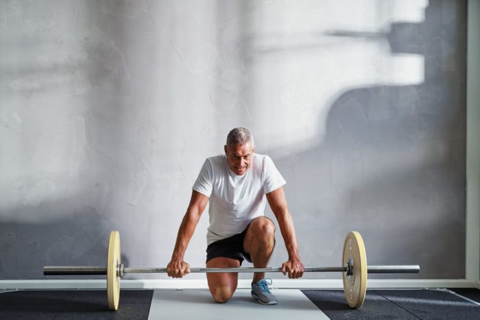 Man kneeling down to pick up a barbell with large weights