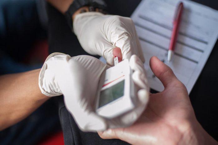 doctor or nurse inserting glucose test strip into glucometer