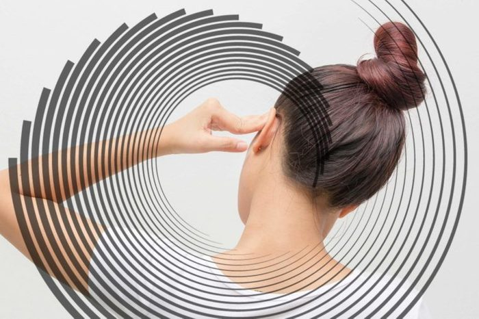 woman from the back, pressing her hand to her ear