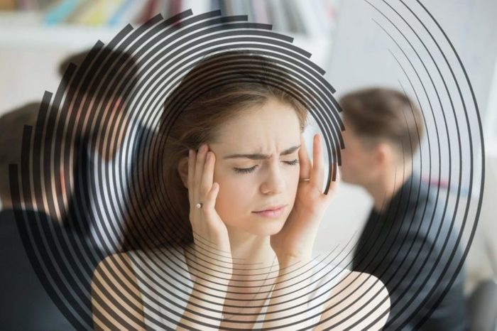 woman with eyes closed, hands at her head