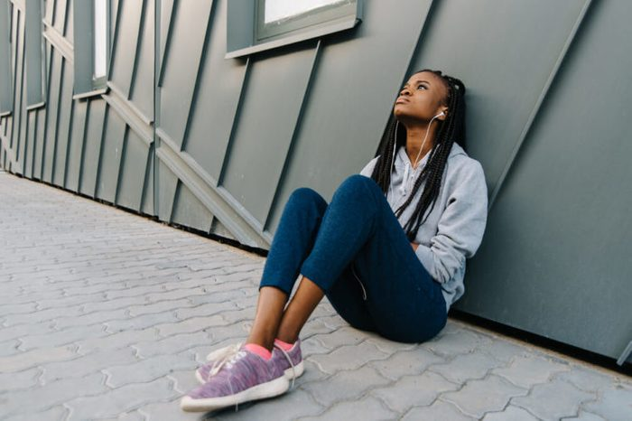 Teenage girl with long braids and earbuds, sitting and listening to music.