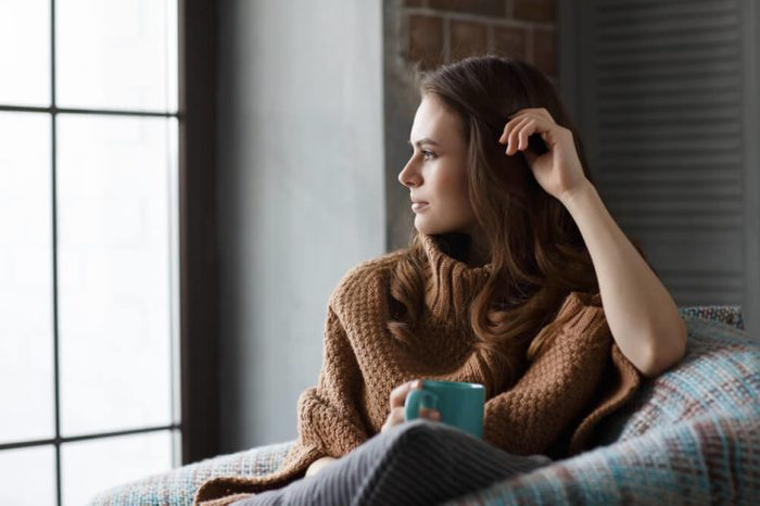 Beautiful girl sitting in an armchair with a mug of coffee looking thoughtfully through a window.