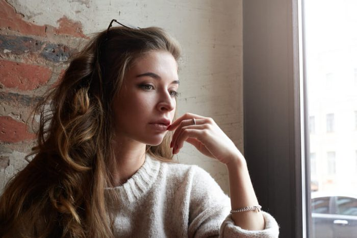 Thoughtful, stylish young female in deep thought.