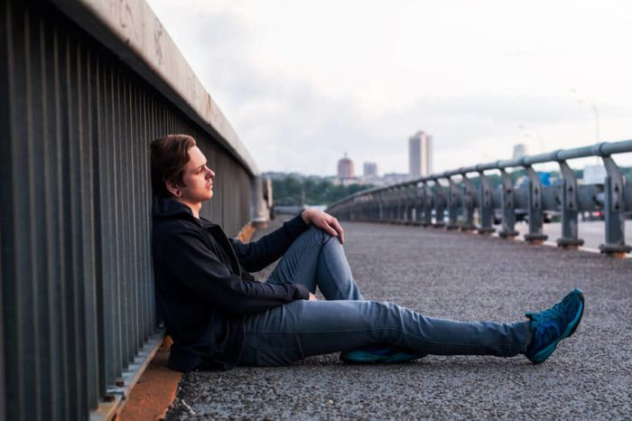 Sad young man is sitting with his back resting against a railing on the waterfront.