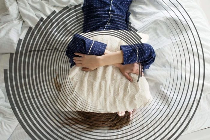 woman in bed on her back, hugging a pillow to her face and chest