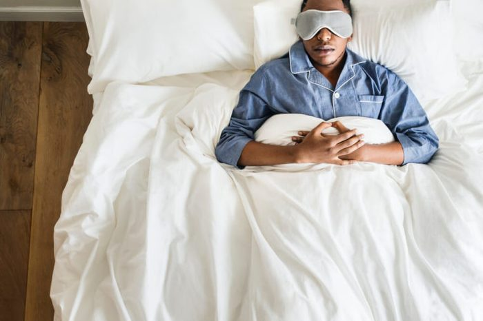 Man sleeping on bed with eye mask.