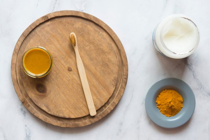 Jar of turmeric spice and toothbrush on a wooden plate.