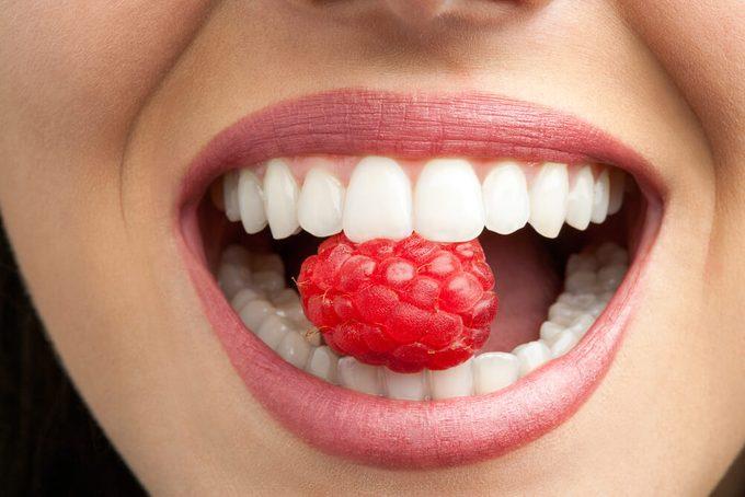 Macro close up of healthy female teeth biting raspberry.