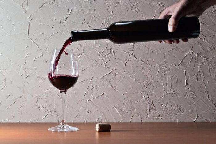 Pouring a glass of red wine.