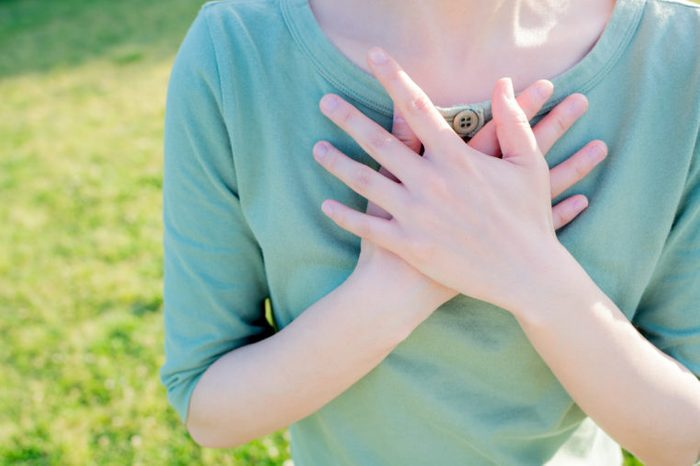 woman hands on chest outdoors