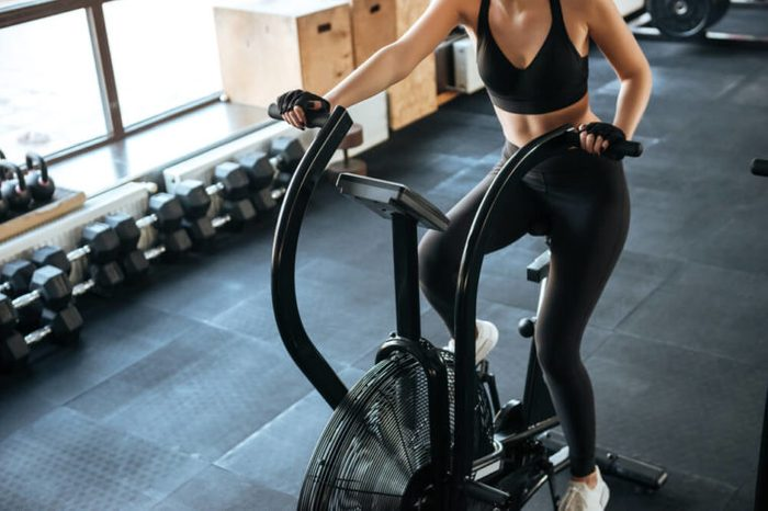 Woman on spinning bicycle at gym.