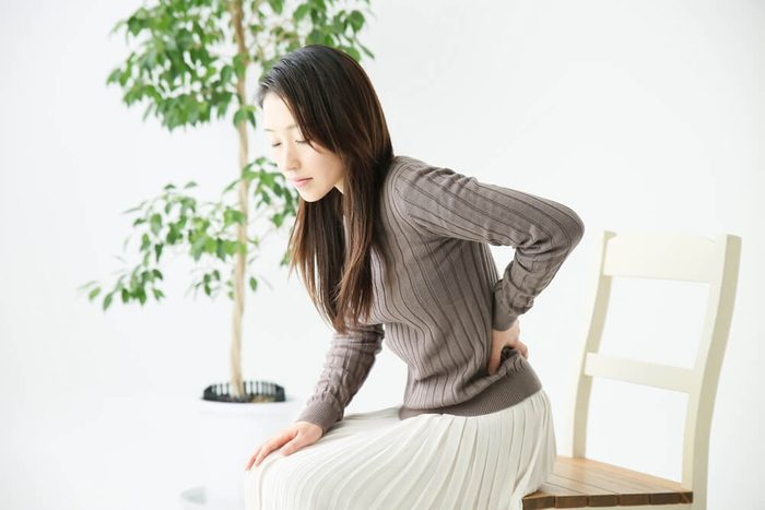 woman holding back pain