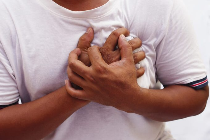Hand Squeeze The Chest In Pain Over White Background