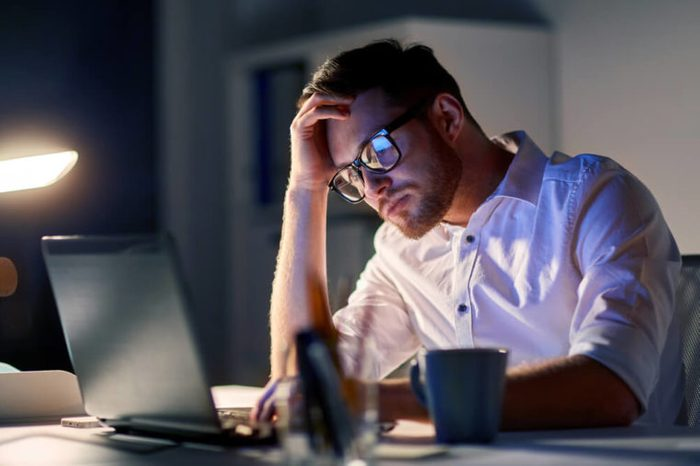 Stressed businessman in glasses with laptop computer working late in the office.