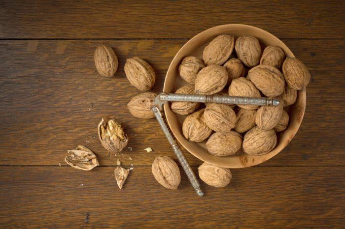 Bowl of walnuts, nut cracker, one opened walnut
