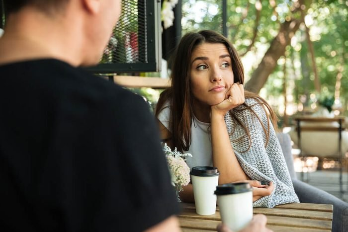 Bored girl drinking coffee with her boyfriend and looking away