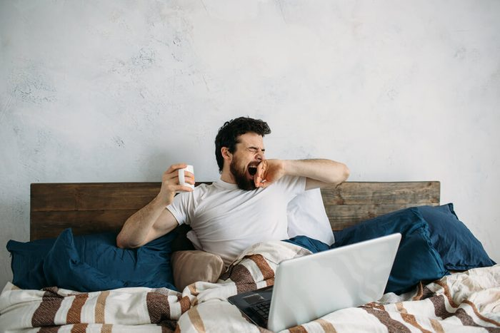 Handsome man lying in bed and warm blanket and stretching and yawning. Sleepy guy has laptop on the top and holding cup with hot tea or coffee in right hand
