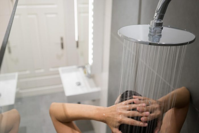 Person enjoying a communal shower in a large cubicle sitting under a large flat shower head letting the water run over their body, close up high angle view from behind