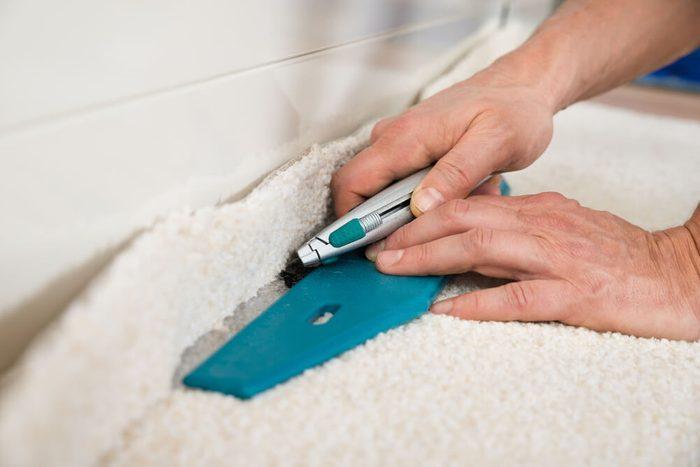 Close-up Of A Craftsman Cutting Carpet With Cutter