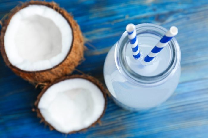 Bottle of coconut water with fresh nuts on wooden background
