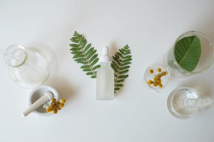 White glass cosmetic bottle with laboratory glassware and leaves