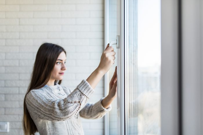 woman closing window