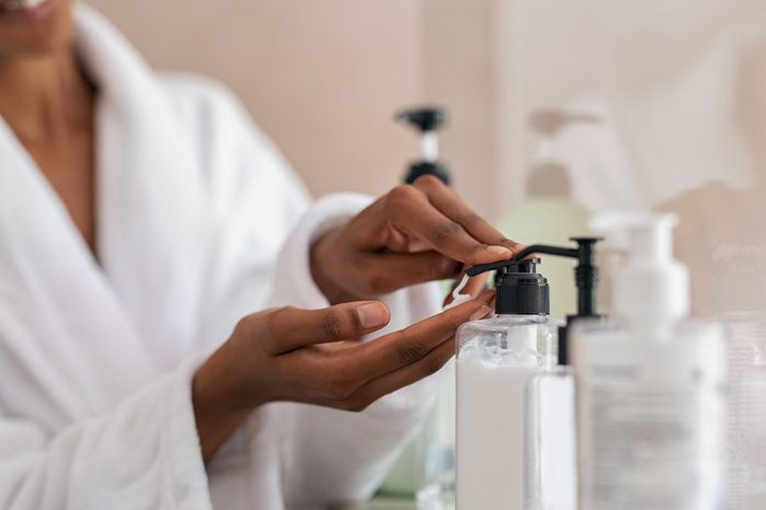 woman taking body lotion from dispenser