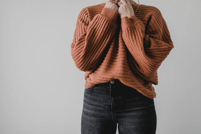 cropped shot of woman's outfit sweater and jeans