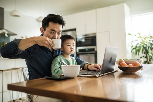 father working at home with son in lap