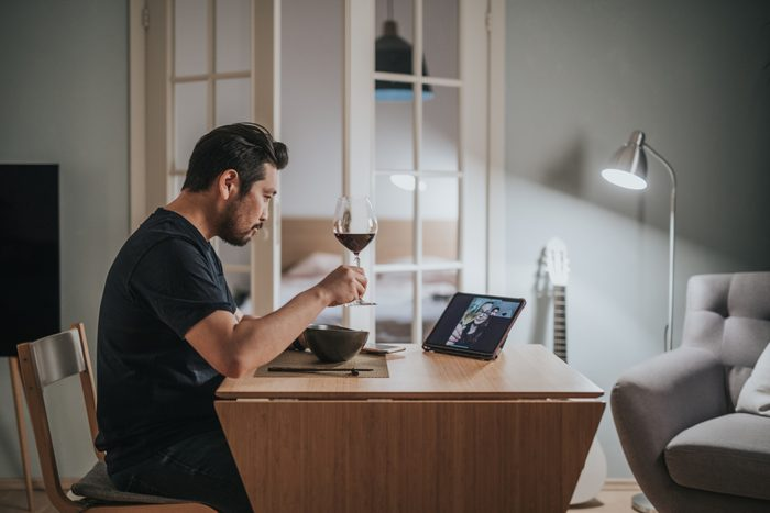man drinking wine during virtual dinner date at home