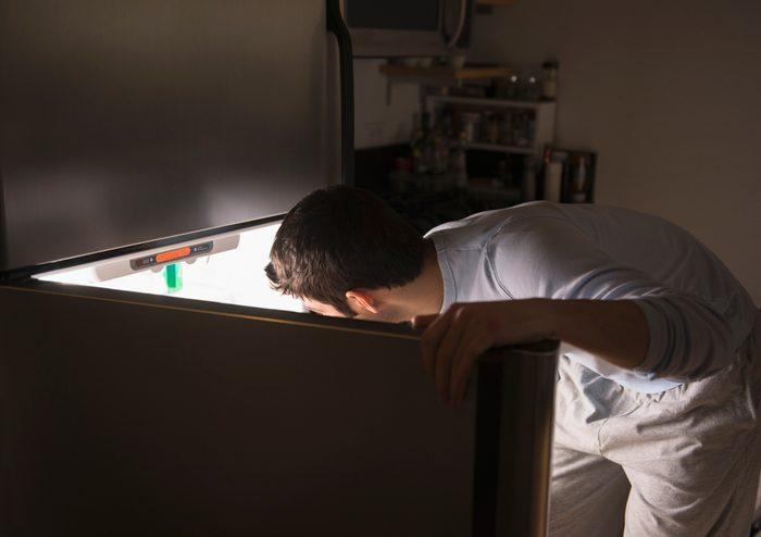 man opening refrigerator at night