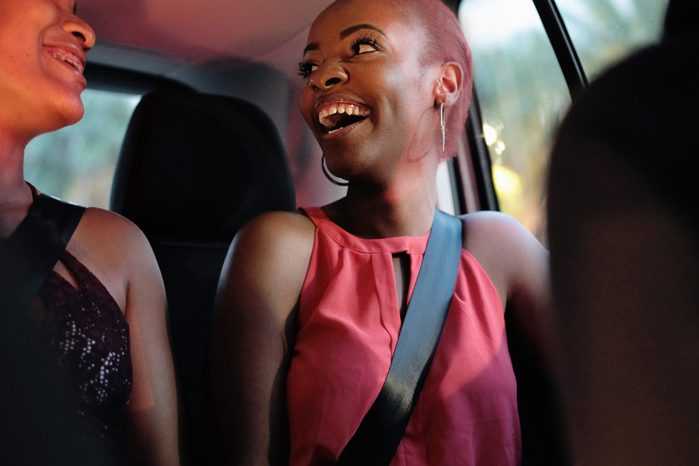 woman in car laughing with friends